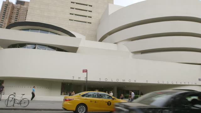 WS PAN Exterior of Guggenheim Museum, traffic moving in foreground / Manhattan, New York City, New York State, United States