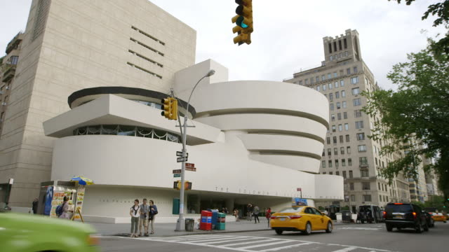 ws pan exterior of guggenheim museum, traffic moving in foreground / manhattan, new york city, new york state, united states - art gallery stock videos & royalty-free footage
