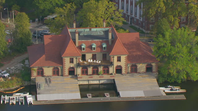 WS AERIAL POV Exterior of Harvard Newell Boathouse on the Charles River, land vehicles moving on street in background / Cambridge, Massachusetts, United States