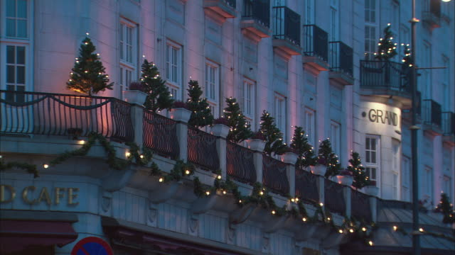 MS Exterior of hotel building with row of small Christmas trees on balcony / Oslo, Norway