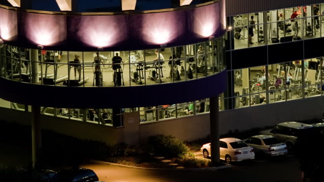 T/L, HA, MS, Exterior of large gym, silhouettes of people exercising seen through glass, night, Universal City, California, USA