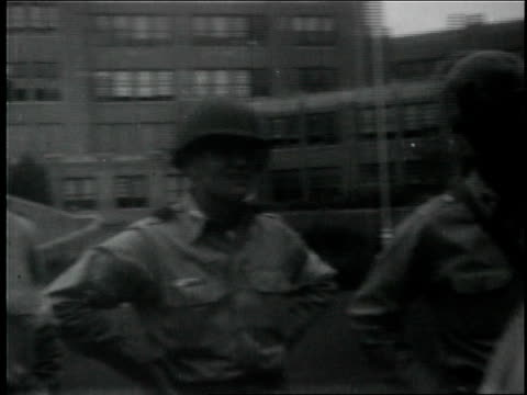 exterior of little rock central high school / students look out windows / national guard stand and patrol outside school / arkansas governor orval... - 長点の映像素材/bロール