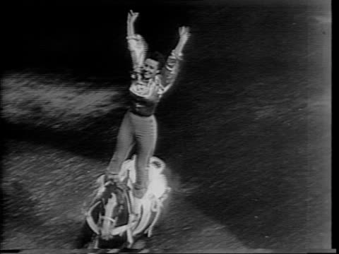 exterior of madison square garden at night / group of horses and riders in arena / stunt woman standing on horse / bronco tosses ride - stunt stock-videos und b-roll-filmmaterial