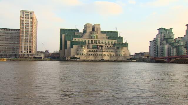 exterior of mi6 headquarters, filmed from across the river thames, london - mi6 stock-videos und b-roll-filmmaterial