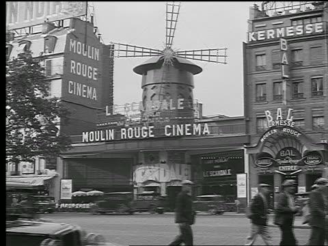 vídeos de stock e filmes b-roll de b/w 1936 exterior of moulin rouge + other nightclub / traffic + people walking in foreground / paris, france - bar local de entretenimento
