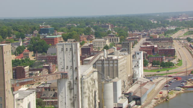 WS AERIAL POV Exterior of old ConAgra Flour Mill with city, cars moving on road / Alton, Illinois, United States