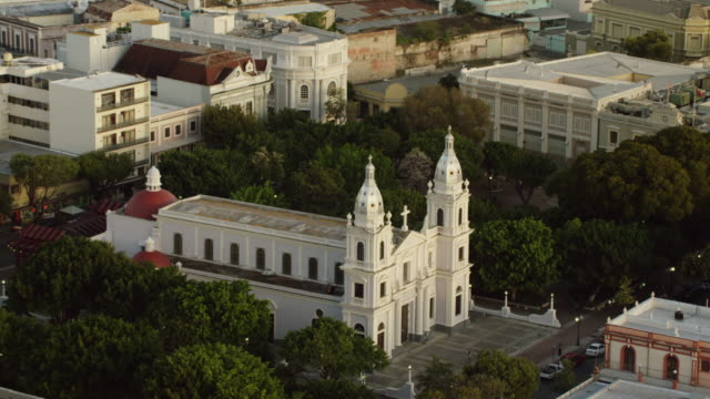 ws aerial pov exterior of ponce cathedral with cityscape / ponce, puerto rico, united states - 宗教上のシンボル点の映像素材/bロール