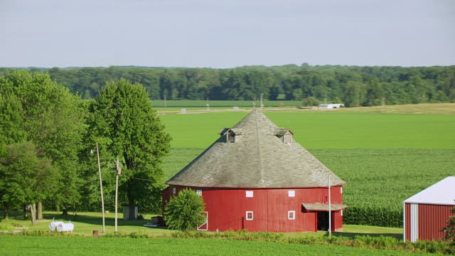 WS AERIAL POV Exterior of round red barn with field and tree area in background / Vigo County, Vincennes, Indiana, United States