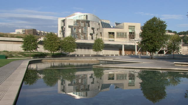 pan exterior of scottish parliament building with pool in front / edinburgh, scotland, united kingdom - parliament building stock videos & royalty-free footage