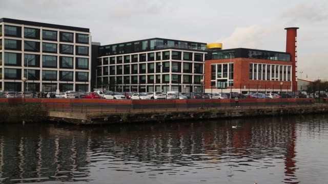 exterior of soapworks building over manchester ship canal at salford quays, salford, greater manchester, uk, on wednesday, february 5, 2020. - bare tree stock videos & royalty-free footage