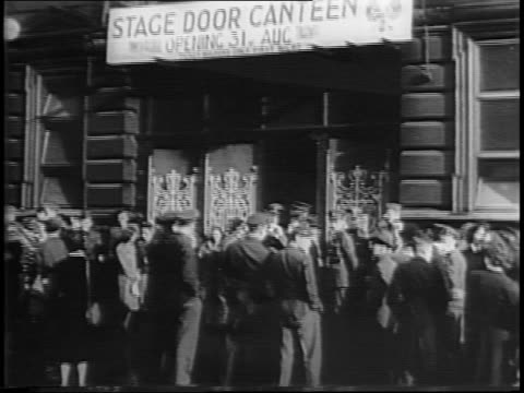 Exterior of Stage Door Canteen / British Foreign Secretary Anthony Eden on stage / crowd applauds / Jack Buchanan and Crosby on stage / Crosby and...