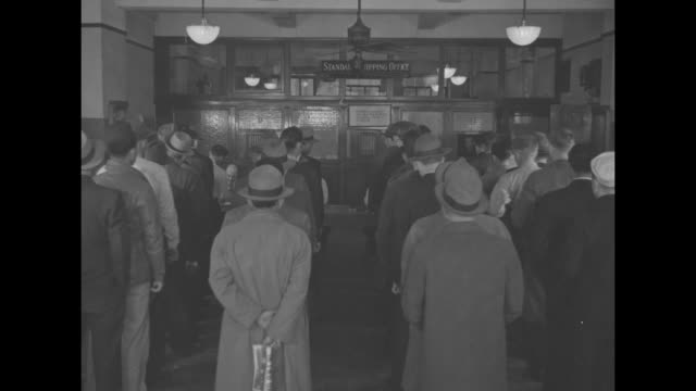 stockvideo's en b-roll-footage met exterior of standard oil building / vs people inside standing in line to sign up to serve on oil tankers / note: exact day not known - in dienst gaan