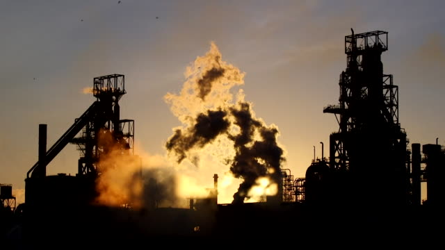 exterior of tata steel in port talbot, steelworks silhouetted against sun, arty and stylised - chimney stock videos & royalty-free footage