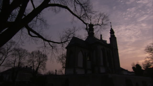 Exterior of the Church of All Saints silhouetted against mauve sky at dusk. Available in HD.
