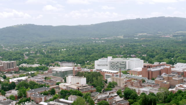 ws aerial pov exterior of the rotunda building with city, forest area in background / charlottesville, virginia, united states - バージニア州点の映像素材/bロール