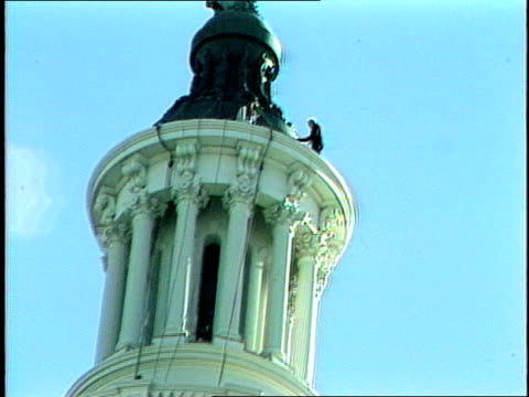 stockvideo's en b-roll-footage met exterior of the us capitol dome during renovations featuring the statue of freedom adult caucasian male laborers working on top of the us capitol... - neoklassiek
