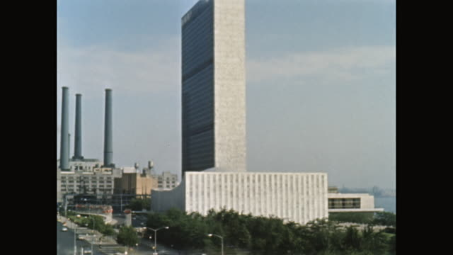 WS Exterior of United Nations Building and cars moving along 1st Avenue, East River in background / Midtown Manhattan, New York City, New York State, United States
