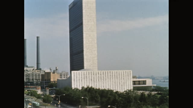 WS PAN Exterior of United Nations Building and land vehicle moving on street / Midtown Manhattan, New York City, New York State, United States