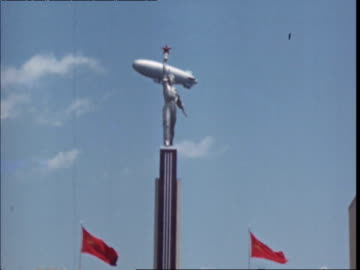 vidéos et rushes de exterior of ussr / soviet pavilion showing statue of soviet worker holding a star and blimp passing by in background / monument with lenin embossed... - communisme