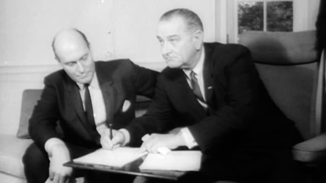 vídeos de stock, filmes e b-roll de exterior of white house / inside white house, president johnson signs a bill / attorney general nicholas katzenbach sits beside him / attorney... - 1965