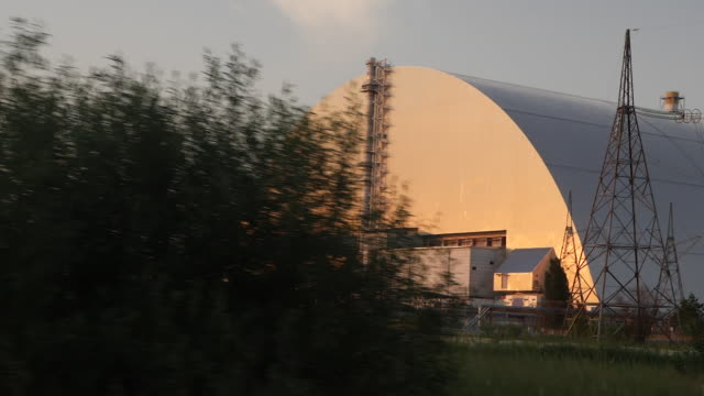 exterior point of view driving shots at sunset passing the sarcophagus or new safe confinement steel casing over chernobyl reactor number 4 and... - metal blend stock videos and b-roll footage