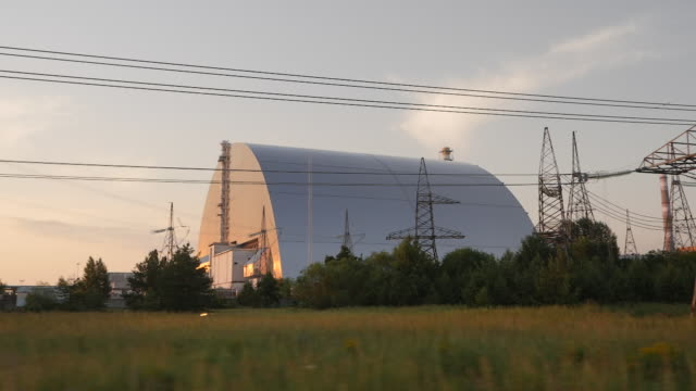 exterior point of view driving shots at sunset passing the sarcophagus or new safe confinement steel casing over chernobyl reactor number 4 and... - number 4 stock videos & royalty-free footage