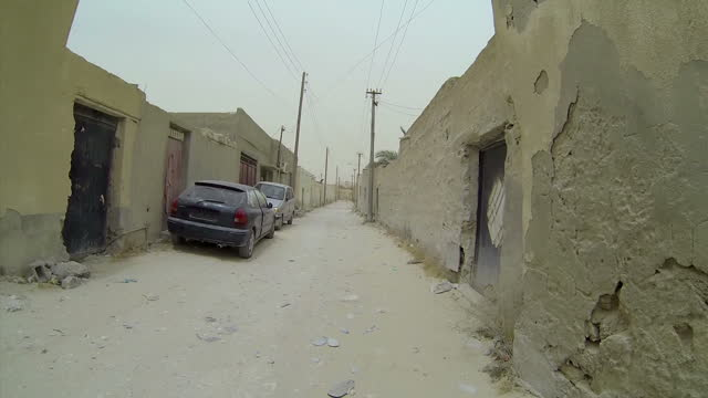 Exterior point of view driving shots of alleys and back roads of a neighbourhood in Zuwarah where migrants are commonly hidden Filmed on June 13 2015...