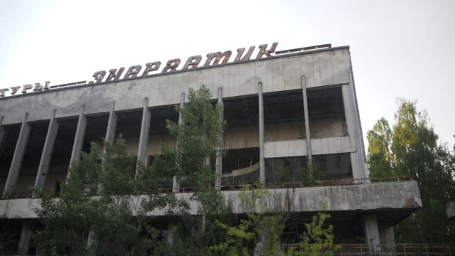 exterior point of view driving shots past derelict abandoned buildings surrounded by overgrown trees and weeds in the city of pripyat on 10 june 2019... - umgeben stock-videos und b-roll-filmmaterial
