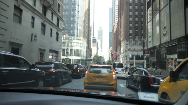 exterior point of view driving shots through central manhattan past other traffic and pedestrians on 10 may 2019 in new york united states - gelbes taxi stock-videos und b-roll-filmmaterial