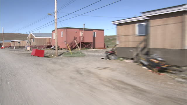 exterior point of view shot from bike traveling through an inuit village in northern canada. on august 25, 2007 in cambridge bay, canada. - inuit bildbanksvideor och videomaterial från bakom kulisserna