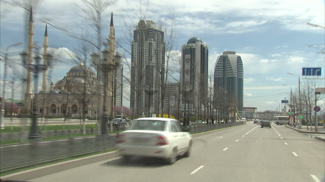 exterior point of view shots driving through streets of grozny grozny street scenes passing mosque in grozny grozny skyscrapers on april 16 2015 in... - grosny stock-videos und b-roll-filmmaterial