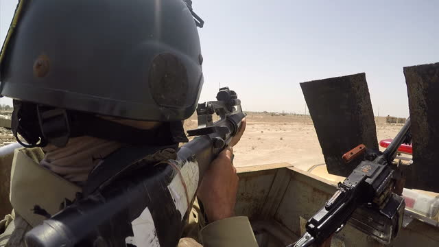 Exterior point of view shots of weapons on the ground and a tank firing explosives towards an ISIS front line on April 22 2015 in Anbar Iraq