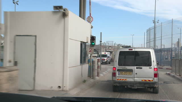 exterior pointofview driving shots through a main checkpoint between israel and the palestinian authority administered west bank passing a sign... - blocco stradale video stock e b–roll
