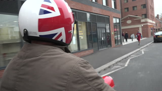 vídeos de stock, filmes e b-roll de exterior pov shot anon man driving a 1963 lambretta scooter moped red and white through the streets of coventry wearing a patriotic union jack... - vanguardista