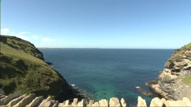 exterior scenic views around tintagel castle as tourists walk along footpaths and stone walls and views over the north atlantic ocean on a sunny day... - north atlantic ocean stock videos & royalty-free footage
