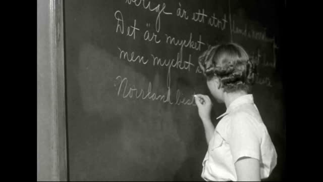exterior school building classroom where Swedish language is being taught teenage girl writing on blackboard