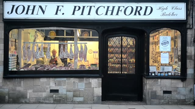 exterior shot a butcher arranges pieces of meat in window in john f pritchard's butcher's shop in the minster town of southwell nottinghamshire on... - butcher stock videos & royalty-free footage