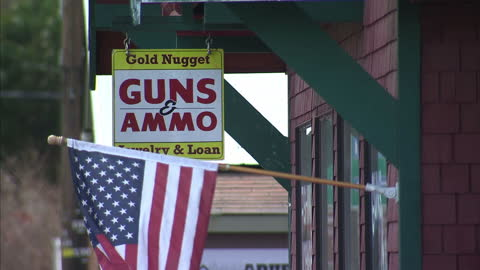 exterior shot american flag blowing in wind in front of guns and ammo sign hanging outside gun store. on 27th march 2014 in oso, washington state,... - 銃器店点の映像素材/bロール