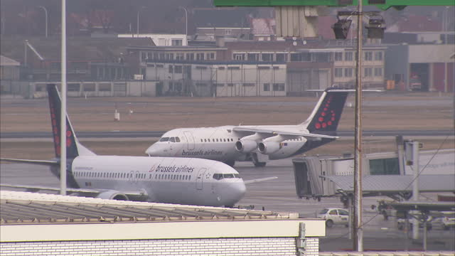 exterior shot brussels airlines passenger plane taxiing to terminal building at brussels airport with brussels airlines plane parked at stand on... - flugpassagier stock-videos und b-roll-filmmaterial