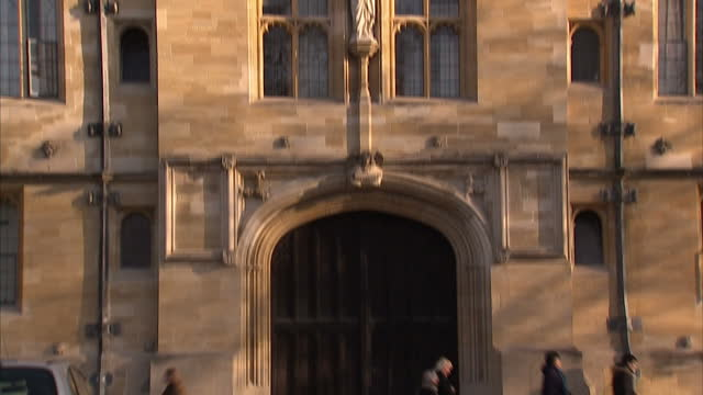 exterior shot cyclist crossing road outside university building exterior shots old oxford university building with gargoyles on display on the walls... - oxford university stock videos & royalty-free footage