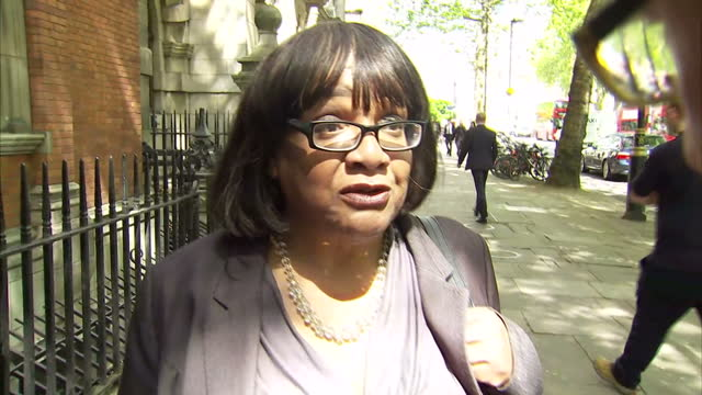 exterior shot diane abbott shadow home secretary walks along towards millbank doorstepped by the media re her figures on putting 10000 more police... - diane abbott stock videos & royalty-free footage