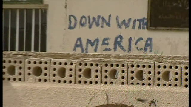 exterior shot 'down with america' written in graffiti on wall with british soldier crouched down next to wall at the start of the 2003 invasion of... - 2003 stock videos and b-roll footage