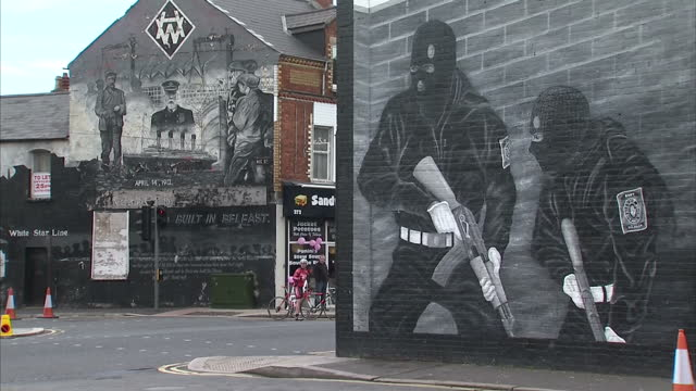 exterior shot giro d'italia competitors cycling past mural depicting ulster volunteer force gunmen on side of building. on may 10, 2014 in belfast,... - darstellen stock-videos und b-roll-filmmaterial