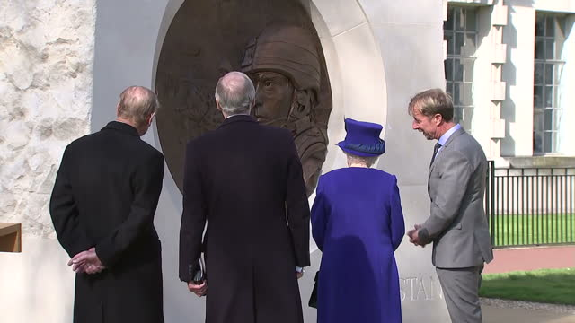 exterior shot her majesty the queen and prince phillip duke of edinburgh take a closer look at war memorial sculpture talking to artist paul day and... - 戦争記念碑点の映像素材/bロール