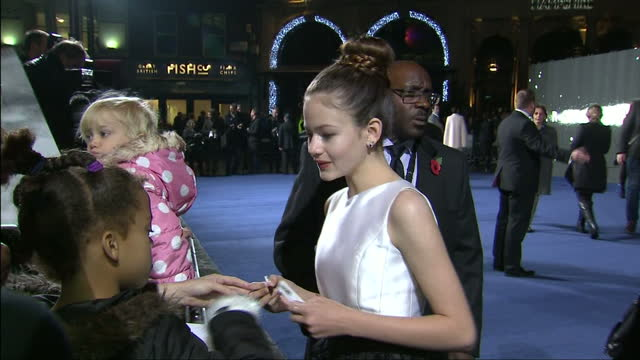 Exterior shot Mackenzie Foy signing autographs for fans on red carpet