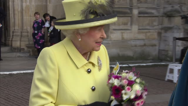 exterior shot mid close up of her majesty the queen smiling and holding flowers wearing a yellow suit, walks with the very reverend john r hall at... - königin elisabeth ii. von england stock-videos und b-roll-filmmaterial