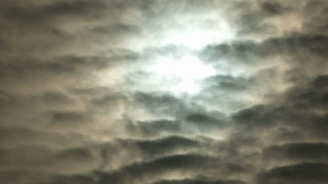 Exterior shot moody atmospheric creepy sky light from sun breaking through clouds ripples clouds dark cloud silhouette shadows clouds moving slowly...