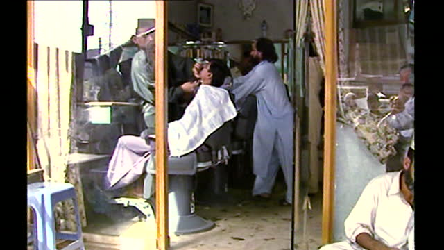 exterior shot of a barber shop in islamabad with a man sitting outside repairing shoes while other men get wet shave inside; 14th september, 2001. - body care stock videos & royalty-free footage