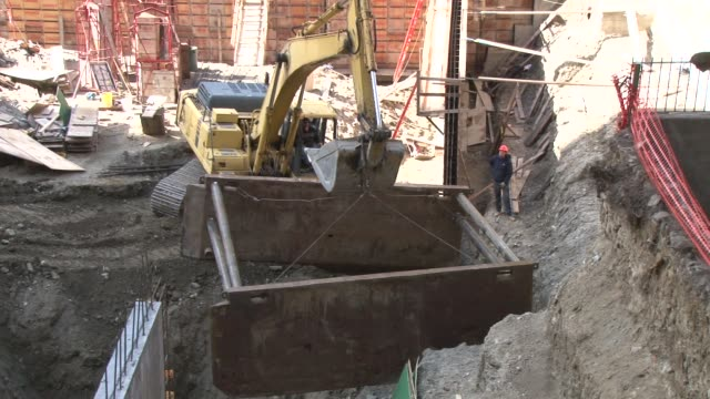 exterior shot of a large steel beam being lowered into a hole at a construction site ws of the machinery in use and cu on the operator of the... - metal blend stock videos and b-roll footage