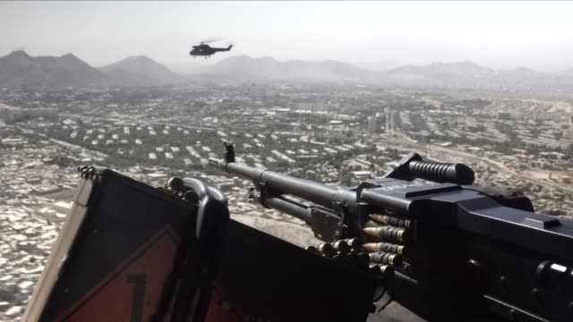 vidéos et rushes de exterior shot of a military helicopter side machine gun and puma model milirary helicopter in flight over kabul on 30th august 2018 in kabul,... - kaboul